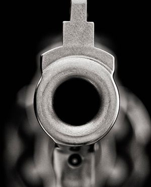 Looking down the barrel of a chrome hand gun, 357 magnum revolver.